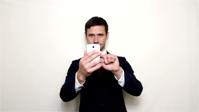 Young handsome businessman taking pictures on a smartphone.