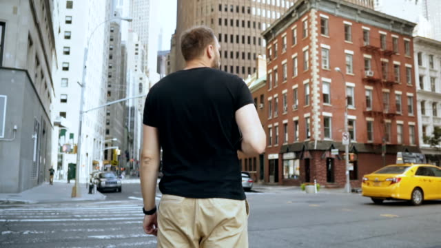 Young handsome businessman with documents standing near road, going to work in office in New York, America. Slow motion