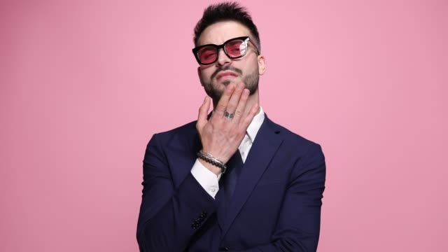 young handsome businessman with sunglasses standing with his back at the camera, turning around, folding hands, running his fingers trough his beard with arrogance on pink background young handsome businessman with sunglasses standing with his back at the camera, turning around, folding hands, running his fingers trough his beard with arrogance on pink background macho stock videos & royalty-free footage