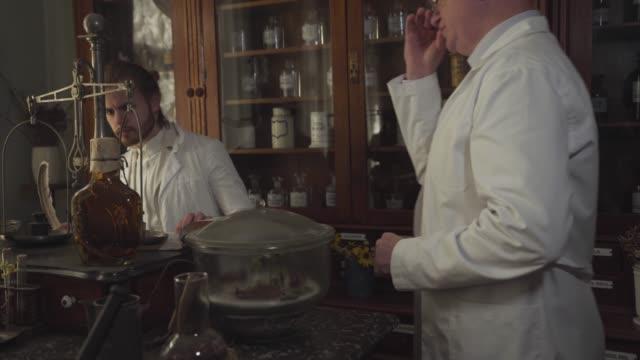junge stattliche kaukasische mann überprüfen medikamente in der alten apotheke, wenn ältere arbeiter kommen. kaukasische apotheker schreiben mit federstift und beratung mit älteren profi. retro, vintage. - antique shop stock-videos und b-roll-filmmaterial