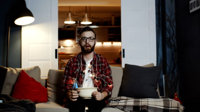 Young handsome geeky Caucasian student man watching movie alone at home with party lights eating snacks slow motion.