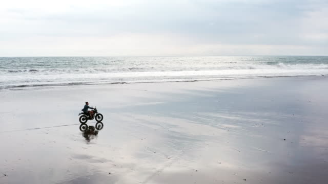 Young handsome hipster man riding modern custom motorcycle racer on the black sand beach near the water. Surfing spot with ocean waves.