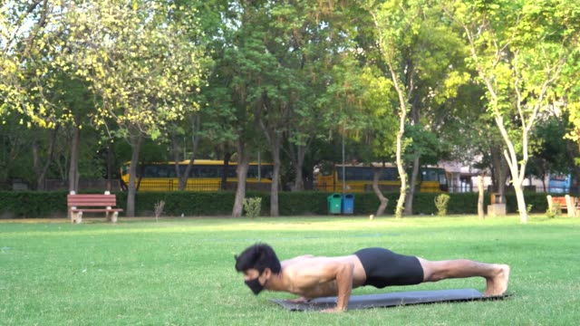 a young handsome indian shredded boy doing pushups in the park wearing a mask for protection from covid-19 - vivid 4k video stock videos & royalty-free footage