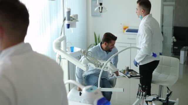 vídeos y material grabado en eventos de stock de joven guapo en dentista - ortodoncista