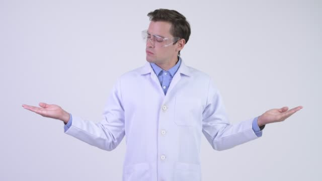 young handsome man doctor as scientist comparing something - due oggetti video stock e b–roll
