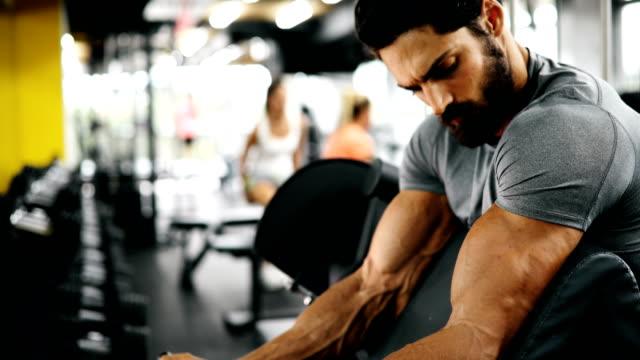 vídeos y material grabado en eventos de stock de hombre guapo joven haciendo ejercicios en gimnasio - entrenamiento con pesas