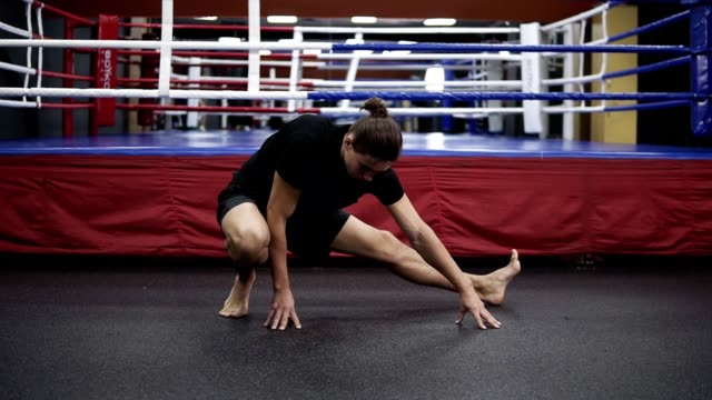 vídeos de stock e filmes b-roll de young handsome man engaged in boxing stretching and preparing before main training. fighter working out at gym, boxing ring behind. front view. slow motion - box separate life