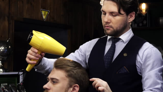 Young handsome man getting his hair dried by a barber video