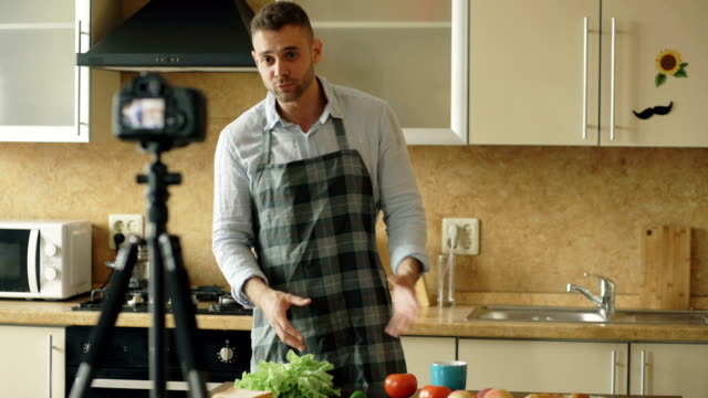 Young handsome man in apron shooting video food blog about cooking on dslr camera in kitchen video
