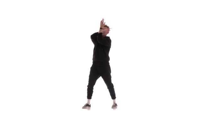 young handsome man in black tracksuit vigorously dancing hip hop, freestyle, street dance, performs complex movements, isolated