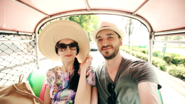 Young handsome man in hat with his girlfriend ride on traditional thai bus songteo taking selfie on smartphone. Couple travel Thailand during their honeymoon video