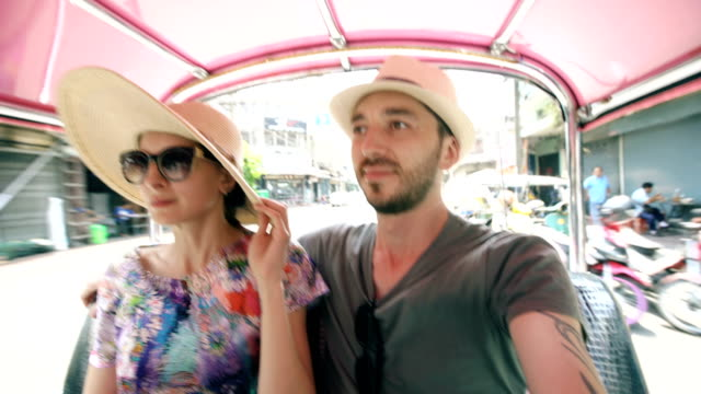 Young handsome man in hat with his girlfriend ride on traditional thai bus songteo . Couple travel Thailand during their honeymoon video