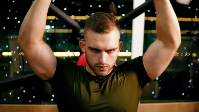 Young handsome man in military t-shirt flexing chest muscles and training his shoulders in the gym. Exercising on duty. Shot in 4k video