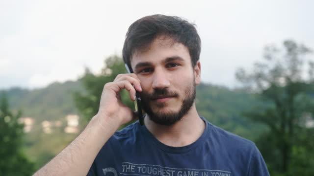 giovane bell'uomo sta parlando con il telefono, guardando la fotocamera, le cose sembrano andare bene - ear talking video stock e b–roll
