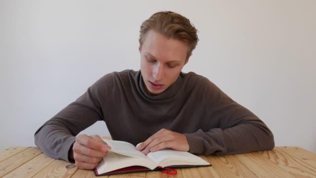 vídeos de stock, filmes e b-roll de jovem bonito lendo um livro em voz alta e olhando para a câmera. estudante. conceito de conhecimento. 4k - salas de aula