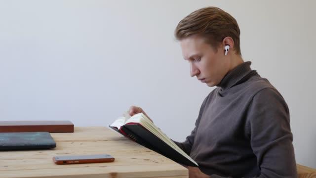 vídeos de stock, filmes e b-roll de jovem bonito lendo um livro. estudante. conceito de conhecimento - salas de aula