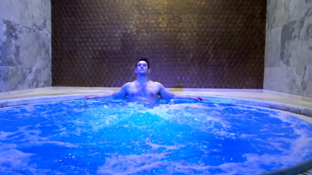 Young Handsome Man Relaxing in hot tub 4K, 29.97P, Real Time resting stock videos & royalty-free footage