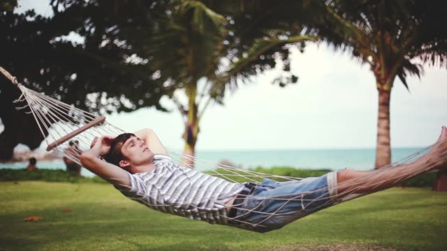Young handsome man relaxing on hammock on beautiful tropical beach. Vacation concept. 1920x1080 Young handsome man relaxing on hammock on beautiful tropical beach. Vacation concept. 1920x1080. hd effortless stock videos & royalty-free footage