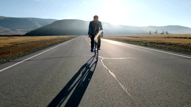 young handsome man riding at vintage bicycle in the country road. sporty guy cycling at the track. male cyclist riding fixed gear bike at highway. healthy active lifestyle 20s fullhd. - cestino della bicicletta video stock e b–roll