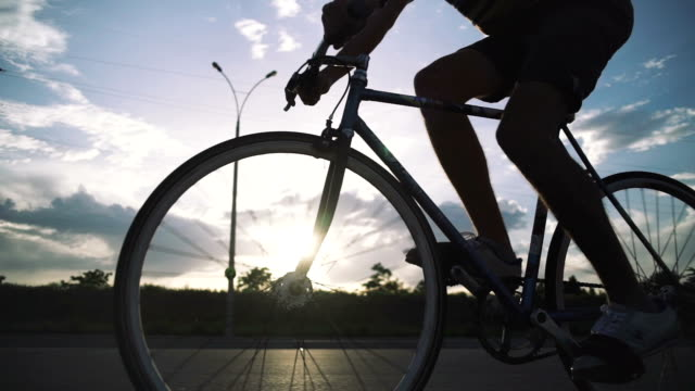 Young handsome man riding fixed gear bicycle during sunset, outdoor. tracking shot. Cinematic silhouette shot video