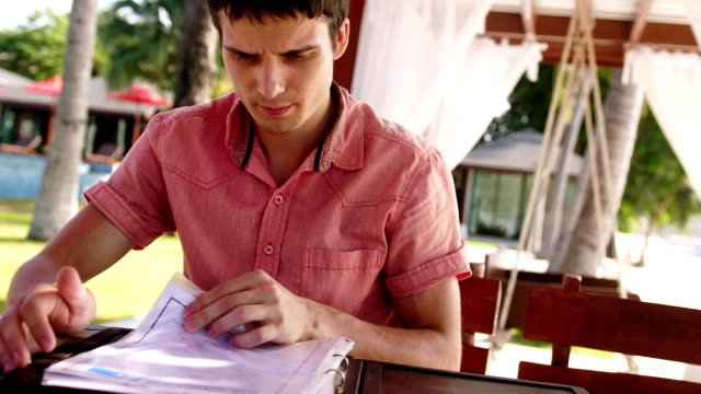 Young handsome man sits in a cafe on the beach scrolls through the menu, wants to make a choice. 3840x2160 Young man sits in a cafe on the beach scrolls through the menu, wants to make a choice. menu stock videos & royalty-free footage