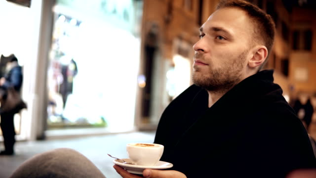 Young handsome man sitting in the cafe in the evening and drinking coffee, spending time in the city centre video