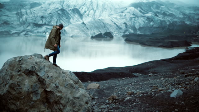 young handsome man sitting on the rock in ice lagoon and looking on glaciers in iceland. tourist stand up and going away - esploratore video stock e b–roll