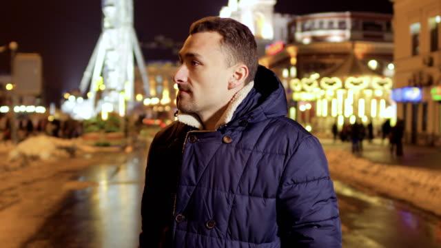 stockvideo's en b-roll-footage met jonge knappe man wacht iemand in het pretpark - portait background