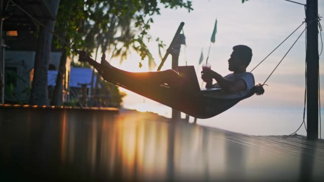 a young, handsome man working on a laptop lying in a hammock with a cocktail in his hands at sunset. - amaca video stock e b–roll