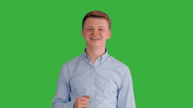 vídeos de stock e filmes b-roll de young handsome men acting in front of a green screen. blond hair, blue shirt and blue trousers. dancing, thinking, turning around and talking to the camera. - homem casual standing sorrir
