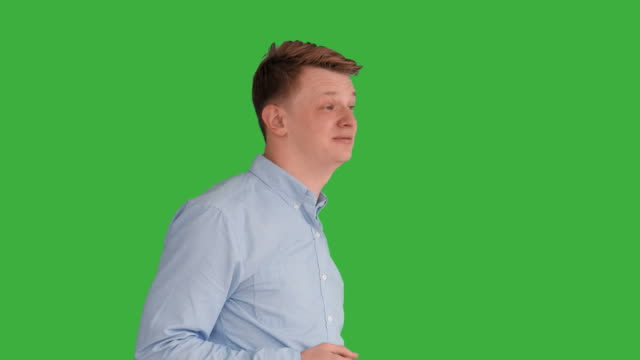 Young Handsome Men Acting in Front of a Green Screen. Blond Hair, Blue Shirt and Blue Trousers. Dancing, Thinking, Turning Around and Talking to the Camera. video