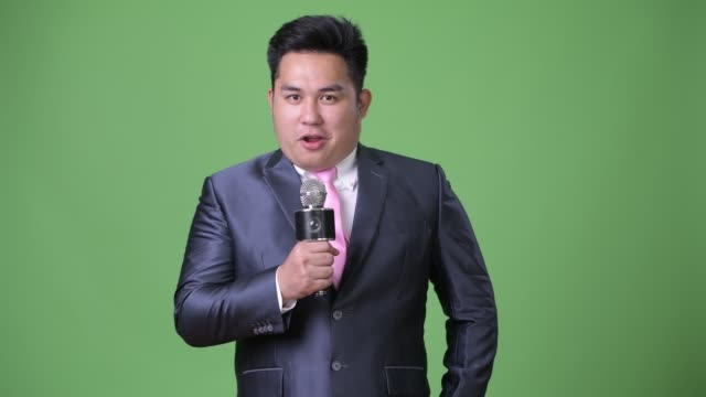 young handsome overweight asian businessman against green background - cantante video stock e b–roll