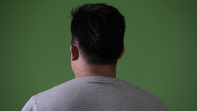 young handsome overweight asian man against green background - testa video stock e b–roll