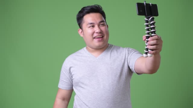 Young handsome overweight Asian man against green background video