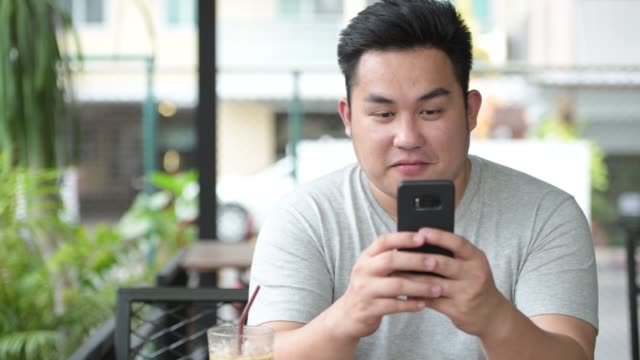 vídeos de stock e filmes b-roll de young handsome overweight asian man relaxing at the coffee shop - etnia filipina