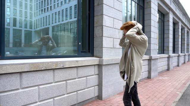 vídeos de stock, filmes e b-roll de jovem bonito elegante é olhar para si mesma na janela e usa o capuz. - moda urbana