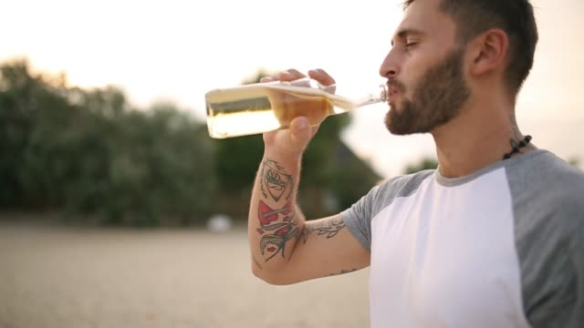 vídeos de stock e filmes b-roll de young handsome tatooed bearded caucasian man drinking beer of glass bottle on the beach during sunset, steadycam shot, slow motion. male quenches thirst with lemonade beverage at sandy sea shore - limonada tradicional