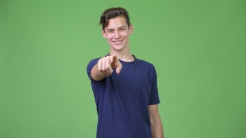 vídeos de stock e filmes b-roll de young handsome teenage boy pointing to camera - mostrar