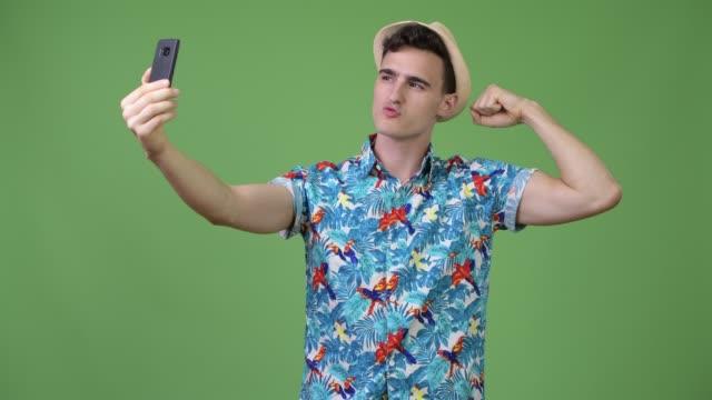 young handsome tourist man taking selfie - napinać mięśnie filmów i materiałów b-roll