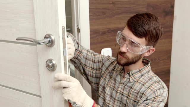 Young handyman in uniform fixing door lock.