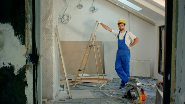 Jonge klusjesman of bouwer permanent in huis kijken naar de camera video