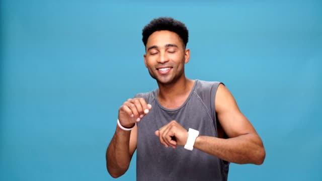 vídeos de stock e filmes b-roll de young happy african man dancing over blue background. - afro americano