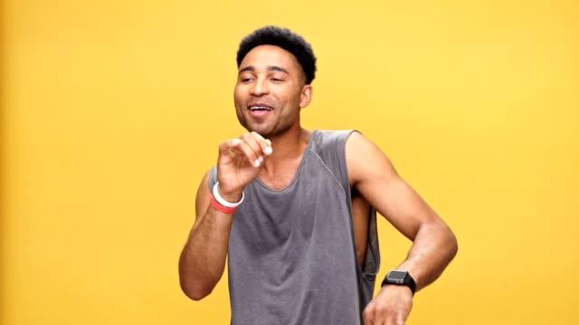 stockvideo's en b-roll-footage met gelukkig afrikaanse jongeman dansen op gele achtergrond. - portrait background