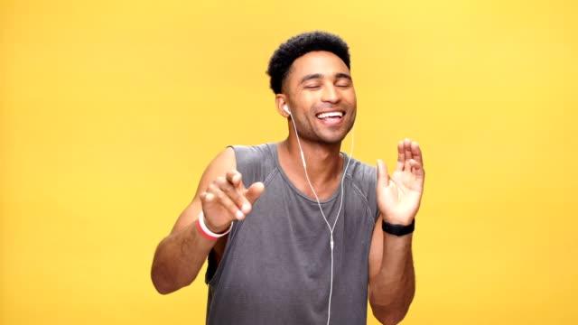 stockvideo's en b-roll-footage met gelukkig afrikaanse jongeman dansen zingen en luisteren muziek op gele achtergrond. - portrait background