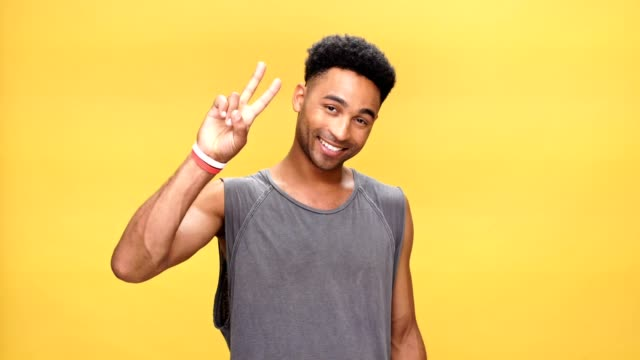 Young happy african man showing peace gesture over yellow background. video