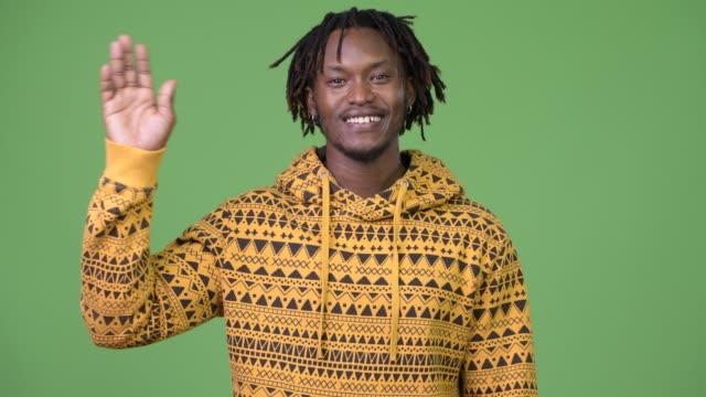 junge afrikanische glücklich hand winken - mann bart freisteller stock-videos und b-roll-filmmaterial