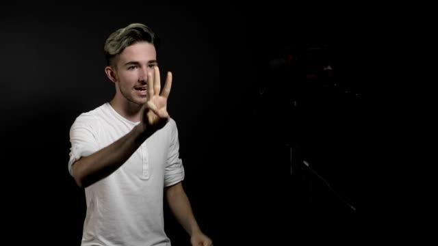 vídeos de stock, filmes e b-roll de vlogger masculino jovem adolescente feliz e alegre, gravação de vídeo com câmera profissional, agradecendo os fãs pelo apoio - blogar