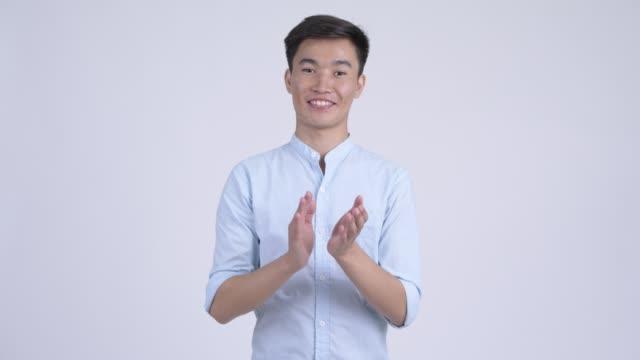 Jovem feliz empresário asiático batendo palmas e recebendo boas notícias - vídeo