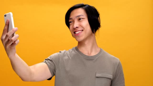 Young happy asian man make selfie by phone isolated over yellow background. video