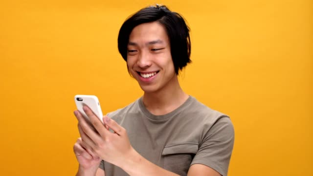 Young happy asian man using phone isolated over yellow background. video